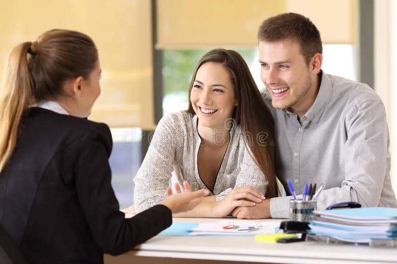 A smiling young couple talking to a estate agents sat at a desk